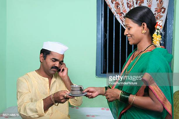 Woman giving her husband a cup of tea