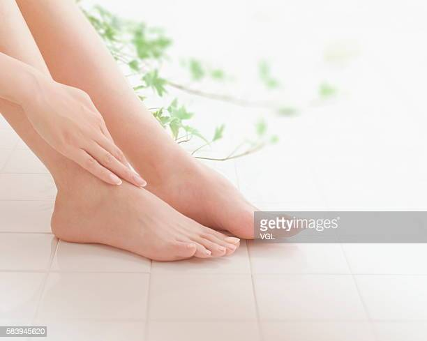 woman giving herself a foot massage - pretty asian feet stock photos and pictures
