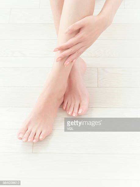 woman giving herself a leg massage - pretty asian feet stock photos and pictures