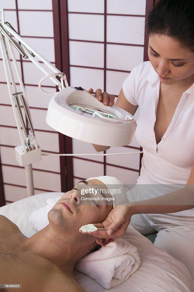 Woman giving man facial : Stockfoto