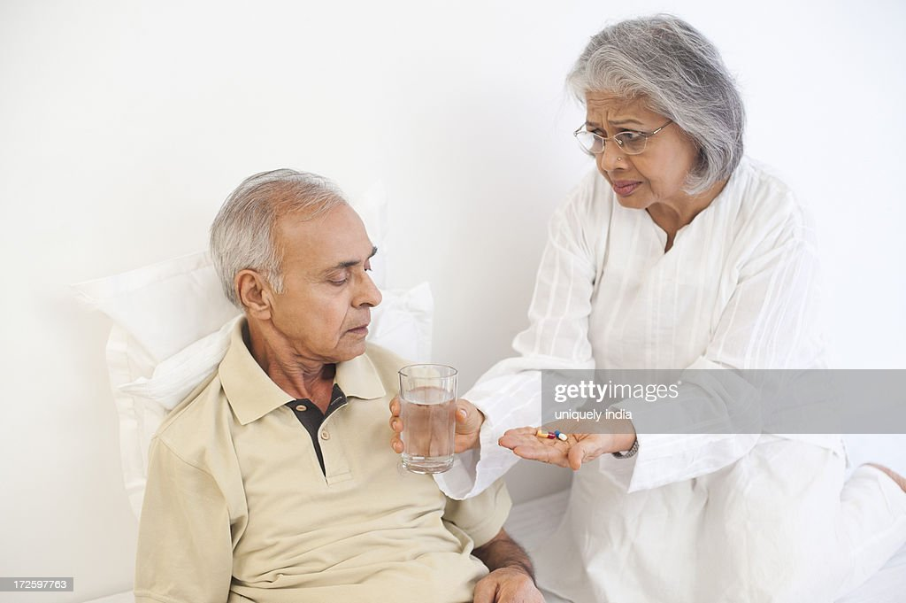Woman giving medicine to her husband : Stock Photo
