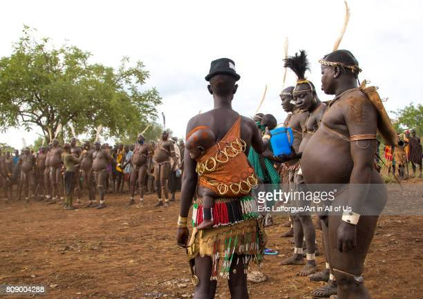 Woman giving milk to Bodi tribe fat men during Kael ceremony Omo valley Hana Mursi Ethiopia on June 2 2017 in Hana Mursi Ethiopia