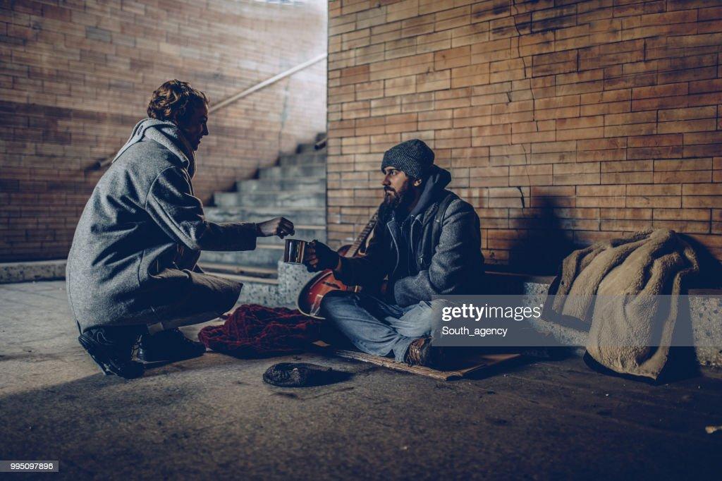 Woman Giving Money To Beggar Man : Stock Photo