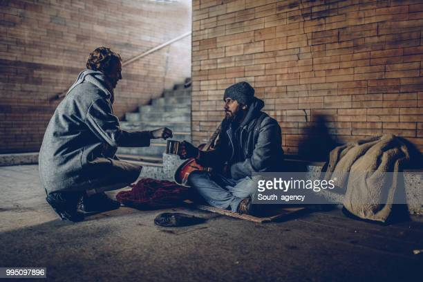 woman giving money to beggar man - homeless foto e immagini stock