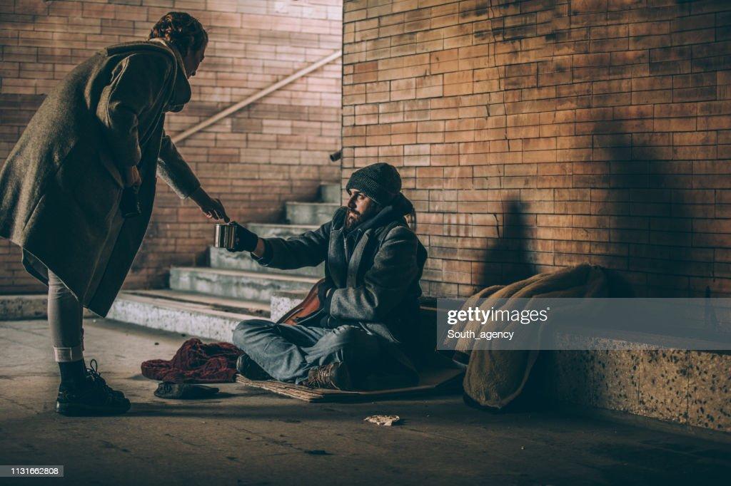Woman Giving Money To Beggar : Stock Photo