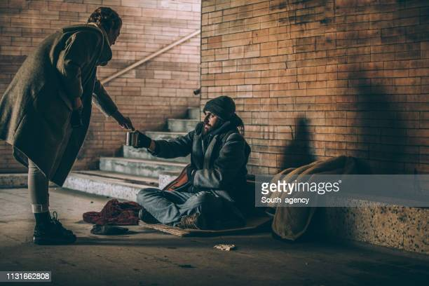woman giving money to beggar - homeless foto e immagini stock