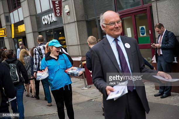A woman giving out a free magazine yawns as a 'Vote Leave' campaigner hands out leaflets by Farringdon Station on June 22 2016 in London United...