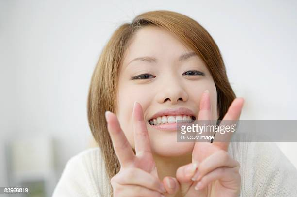 Woman giving peace gesture, smiling