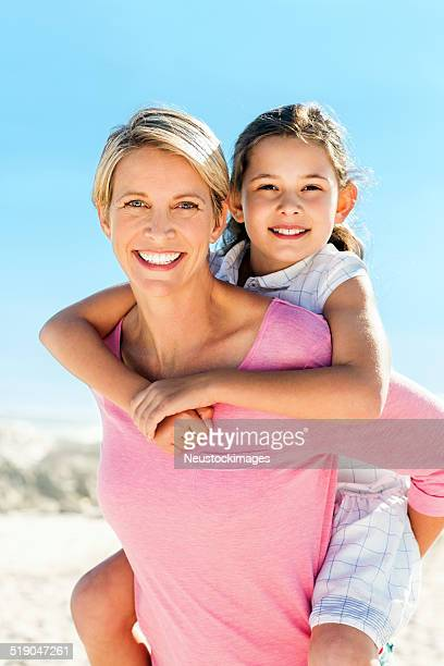 Woman Giving Piggyback Ride To Daughter At Beach