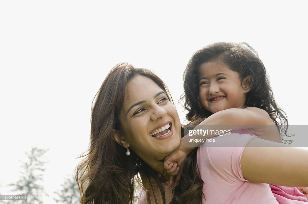 Woman Giving Piggyback Ride To Her Daughter Stock Photo