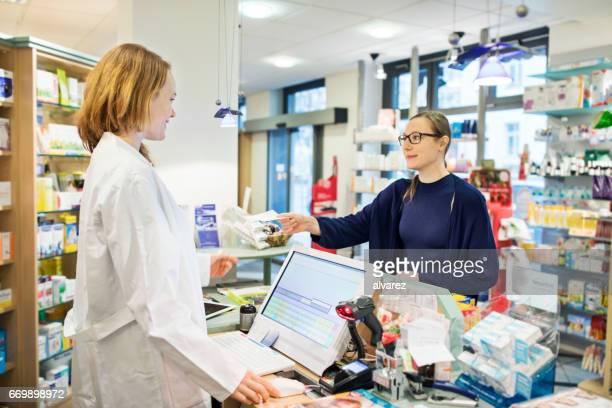 Frau geben Rezept Apotheker im store