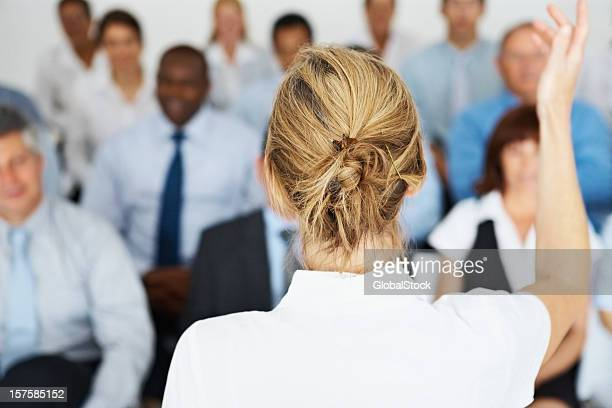 Woman giving presentation to business team