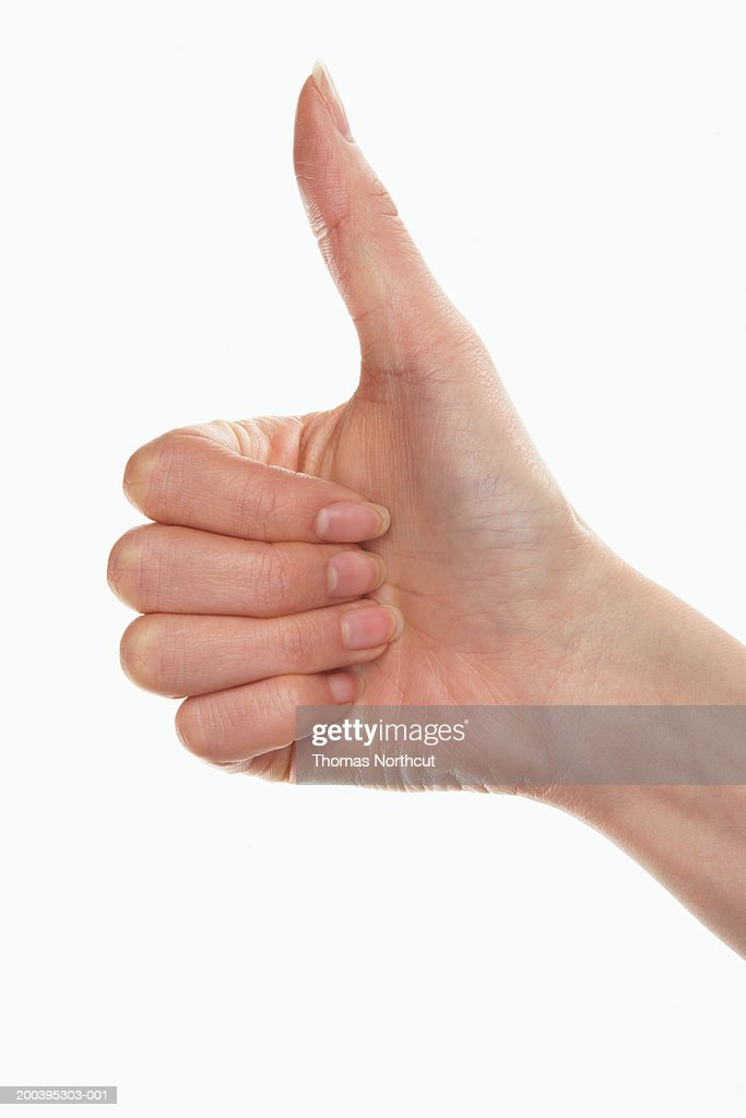 Woman giving thumbs up (focus on hand) : Stock Photo