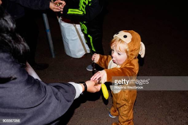 Woman giving treats to Caucasian boy wearing a bear costume
