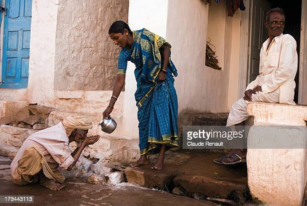 Woman giving water and food to a poor personn in Badami. I