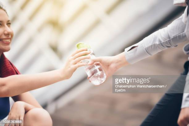 Woman Giving Water Bottle To Female Outdoors