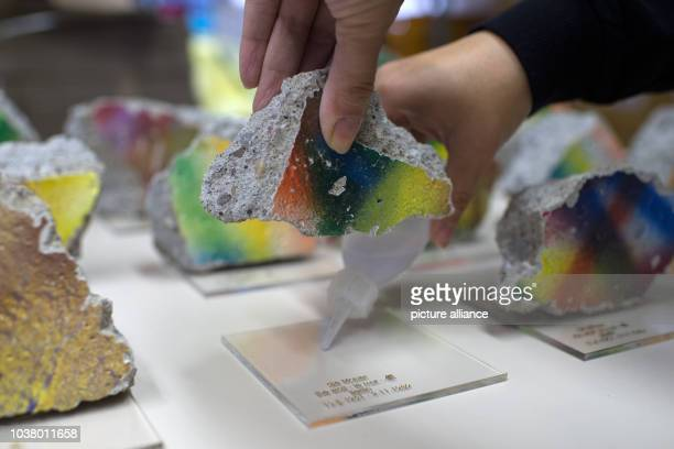 A woman glues a piece of the Berlin Wall to an acrylic plate at Pawlowski a wholesale souvenir supplier inBerlin Germany 04 November 2014 The...