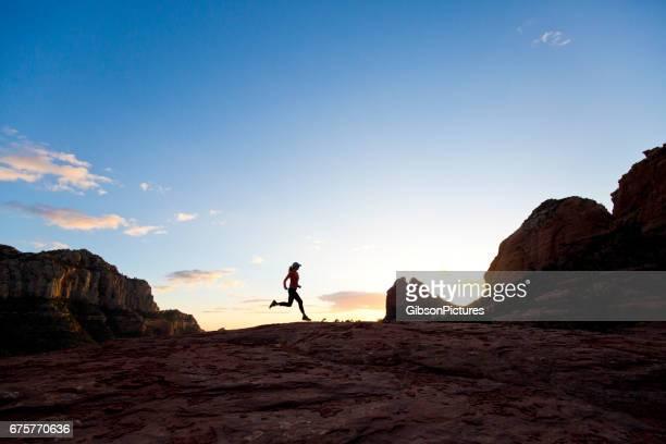 uma mulher vai para uma pista de cross-country executar ao pôr do sol em sedona, arizona, eua. - usa - fotografias e filmes do acervo