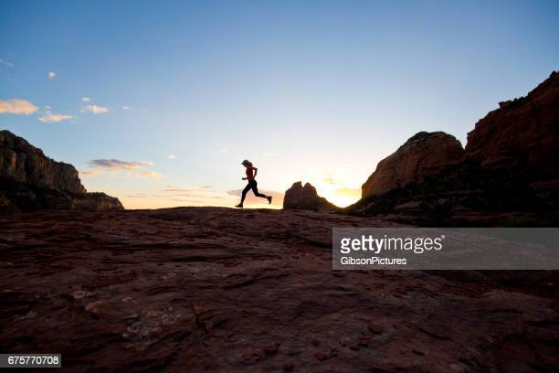 a woman goes for a cross-country trail run at sunset in sedona, arizona, usa. - cross country running stock pictures, royalty-free photos & images
