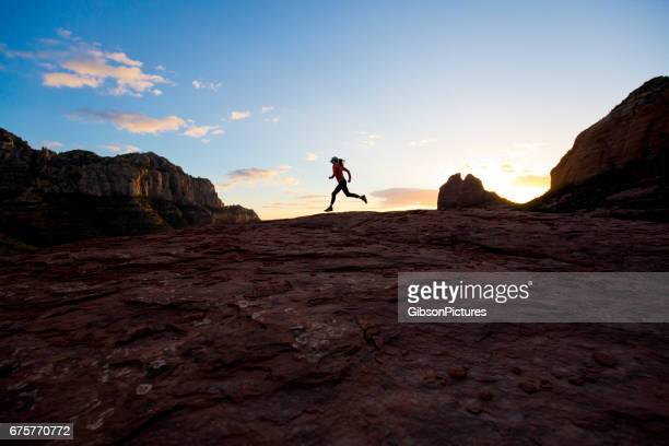 A woman goes for a cross-country trail run at sunset in Sedona, Arizona, USA.