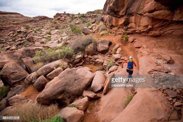 a woman goes for a cross-country trail run near moab, utah, usa. - rocha vermelha imagens e fotografias de stock