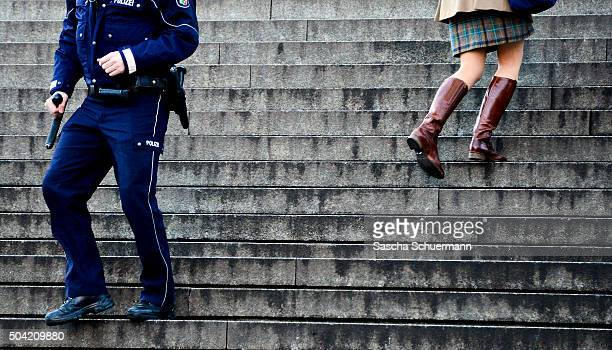 A woman goes past to on an policeman on the stairs between Hauptbahnhof main railway station and Cologne Cathedral on January 9 2016 in Cologne...