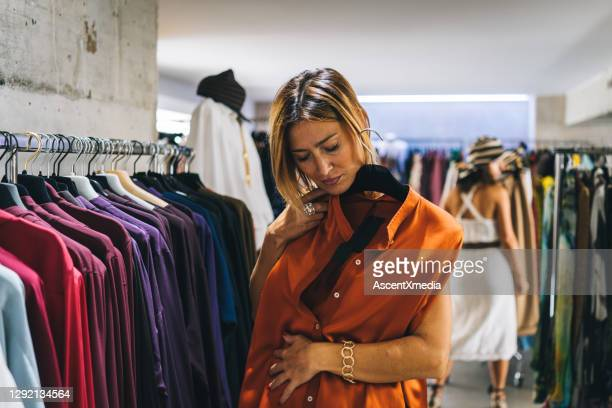 woman goes shopping for clothes for the upcoming season - shirt stock pictures, royalty-free photos & images