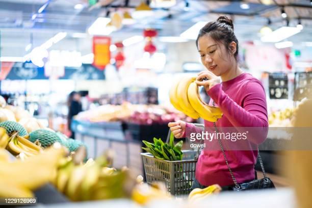 woman goes shopping in supermarkt - bancarella di verdura foto e immagini stock
