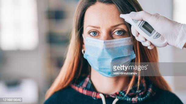 woman goes through a temperature checks before going to work in the office and wearing medical face mask during covid-19 - mascherina antipolvere foto e immagini stock
