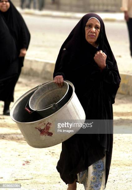 A woman goes to collect water in the Iraqi town of Basra