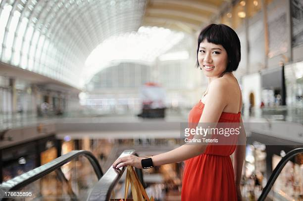 Woman going down an escalator at a mall