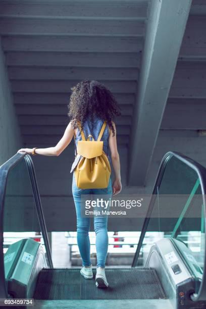 Woman going down an escalator at a mall