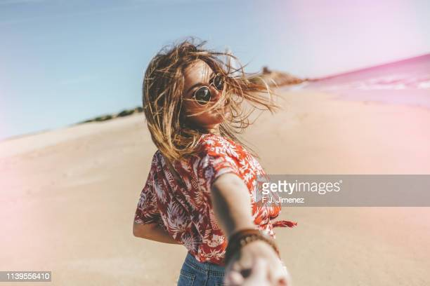 woman going from the hand of the photographer on the beach - minirok stockfoto's en -beelden