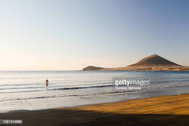 Woman going into water in El Médano beach, in south of Tenerife island (Canary Islands, Spain)