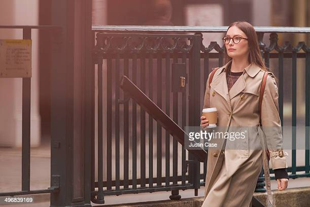 woman going out of a tube station holding coffee