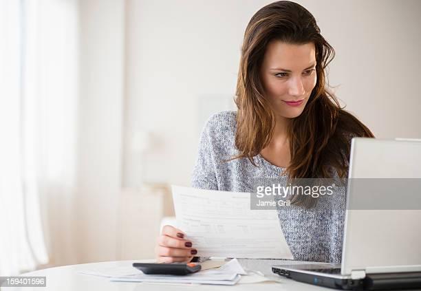 woman going over bills with laptop computer - finanças - fotografias e filmes do acervo
