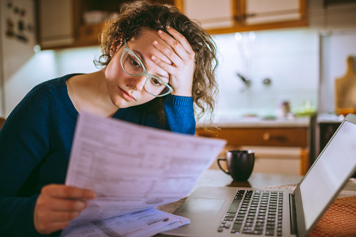 Woman going through bills, looking worried 1013076770