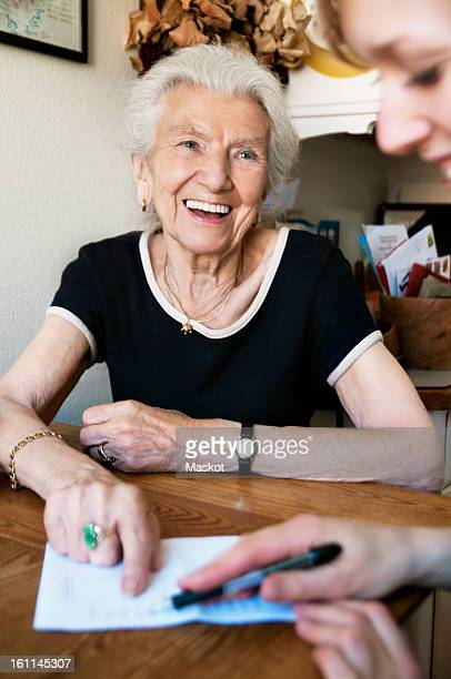 Woman going through paper with elderly lady