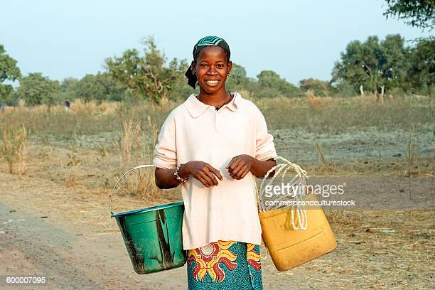 a woman going to fetch water in a creek - femme mali photos et images de collection