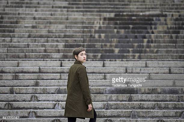 woman going up stairs - looking over shoulder stock pictures, royalty-free photos & images