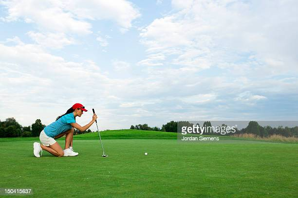 A woman golfing on a summer day.