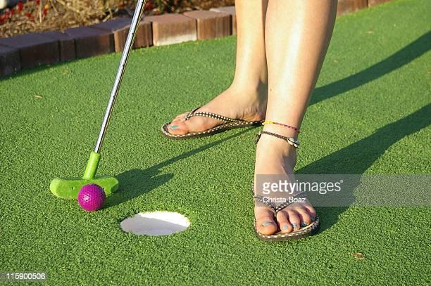 Woman golfing on mini golf course