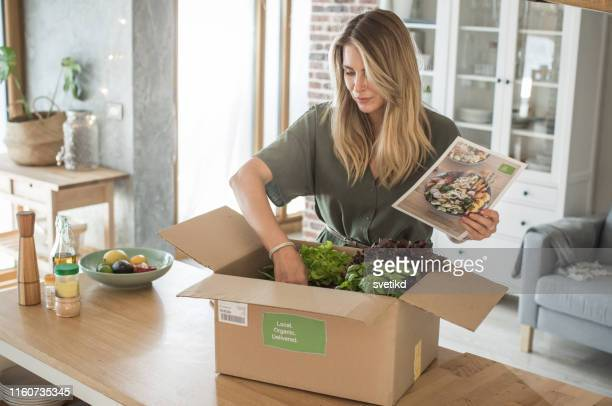 woman got package from meal delivery service. - grocery delivery stock pictures, royalty-free photos & images