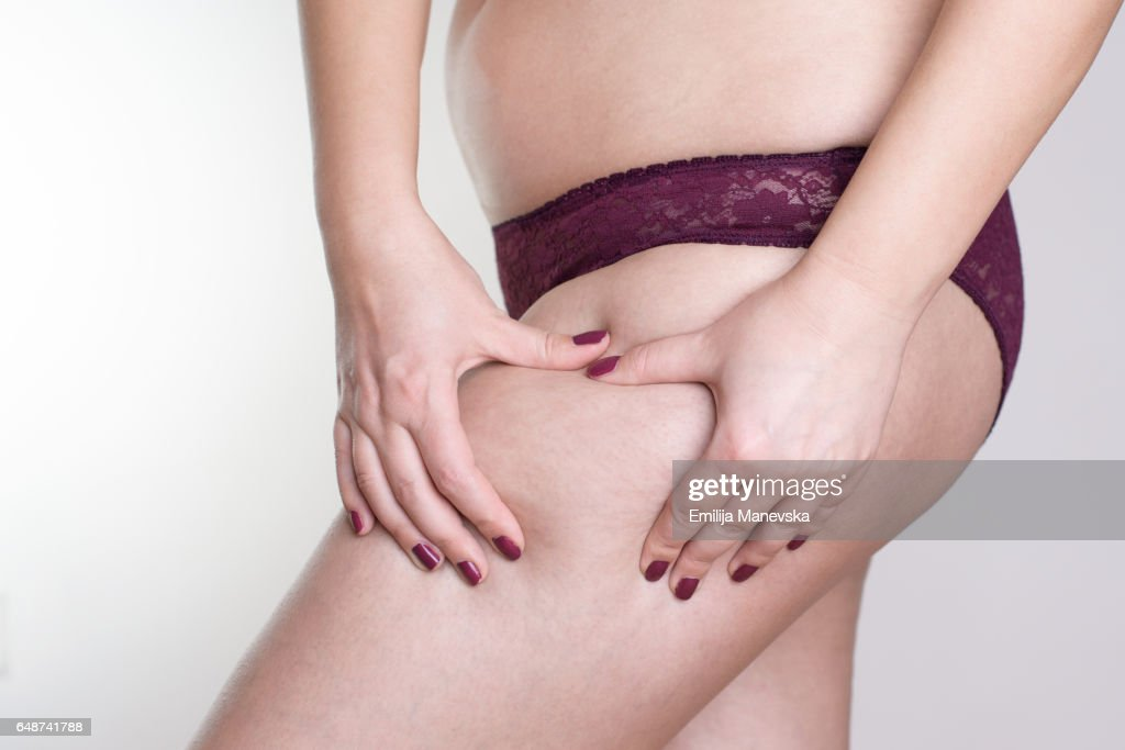 Woman grabbing at her buttocks : Stock Photo