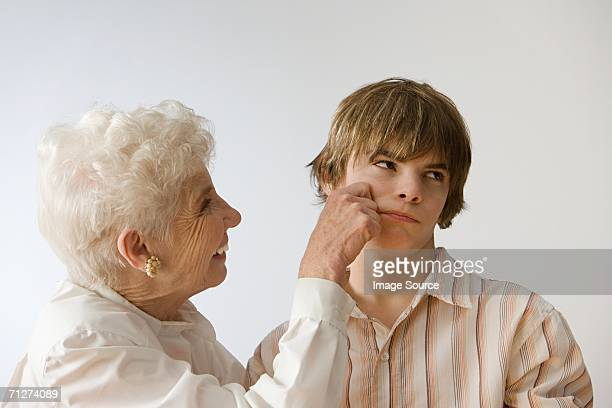 woman grabbing grandson's cheek - cheek stock pictures, royalty-free photos & images