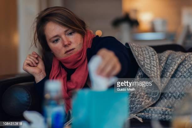 woman grabing tissue paper. - influenza virus stock-fotos und bilder