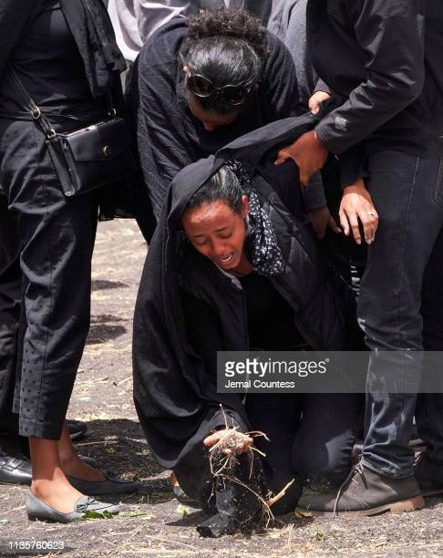 A woman grabs a handful of earth as mourners visit the crash site of Ethiopian Airlines Flight ET302 on March 14 2019 in Ejere Ethiopia All 157...