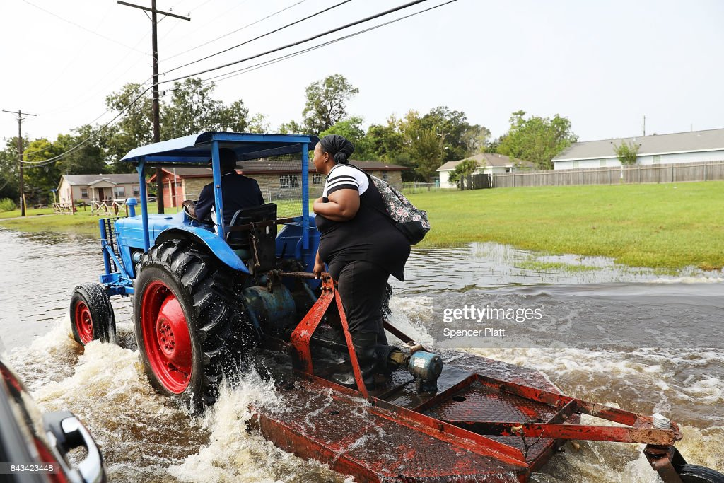 A woman grabs a ride on a tractor through high water along a street in Orange as Texas slowly moves toward recovery from the devastation of Hurricane Harvey on September 6, 2017 in Orange, Texas. Almost a week after Hurricane Harvey ravaged parts of the state, some neighborhoods still remained flooded and without electricity. While downtown Houston is returning to business, thousands continue to live in shelters, hotels and other accommodations as they contemplate their future.