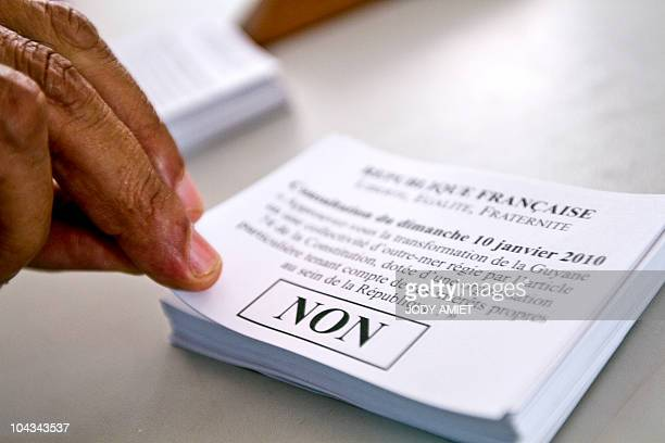 A woman grabs ballots in the polling station of Cayenne on the French South American territory of Guiana on January 10 for the referendum on the...