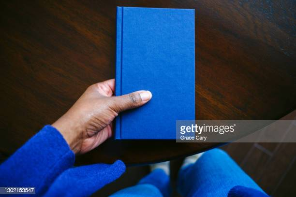 woman grabs book from table - book stock pictures, royalty-free photos & images